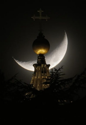 The moon is seen behind a dome of St. Peter's Basilica at the Vatican, Saturday, March 16, 2013. Province of Rome Lazio